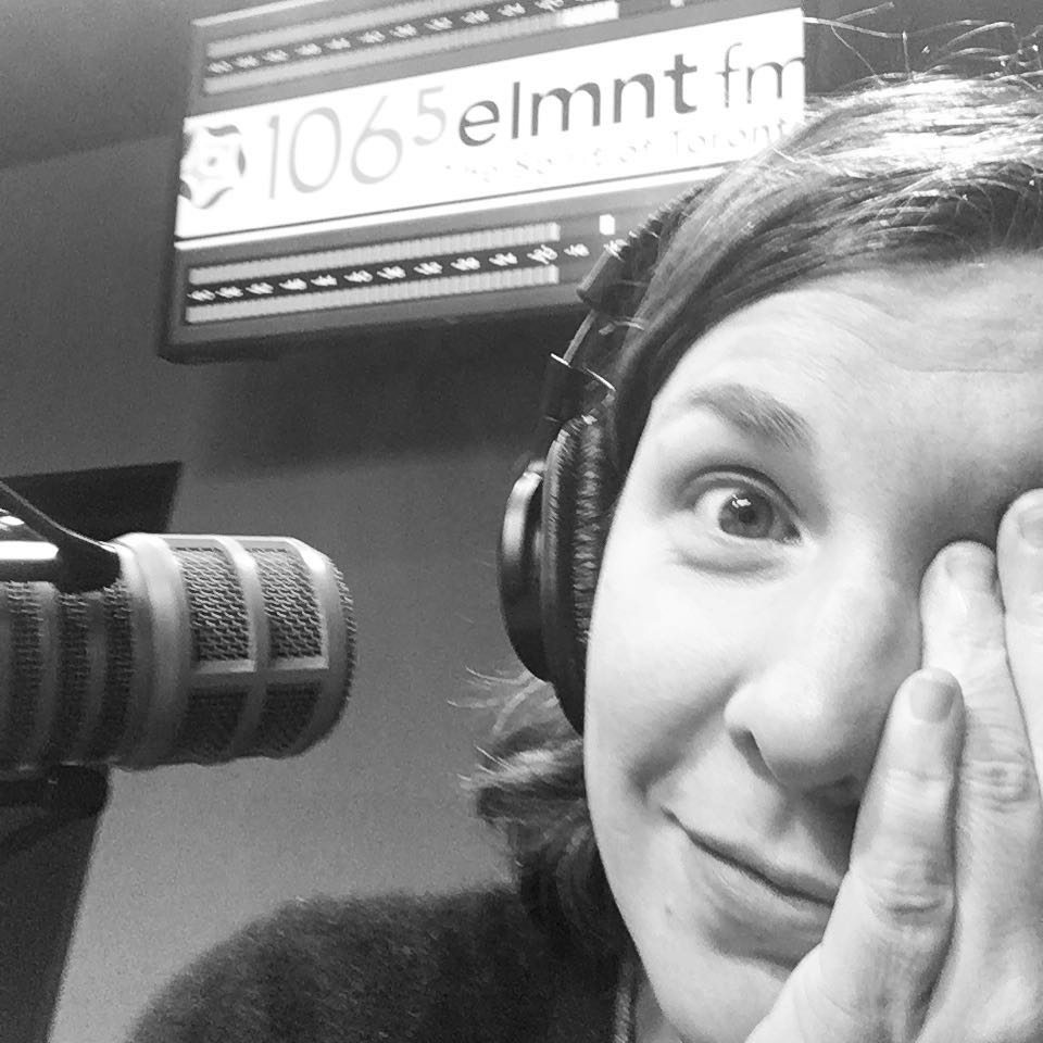 Black and white photo of Christa covering half her face with her hand. A sign in the back says 106.5 ELMNT FM