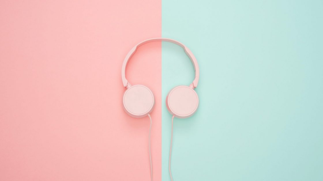 a pair of pink colour headphones against a split pink and mint-green background